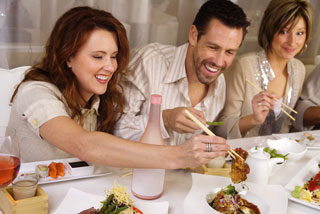 Three people eating with chopsticks, two of whom are laughing