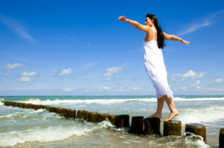 A woman balances on a set of concrete pier posts that extend into the ocean