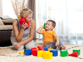 A mother and her son playing with toys and looking at each other