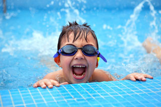 A young boy with swimming goggles grins over the edge of a pool