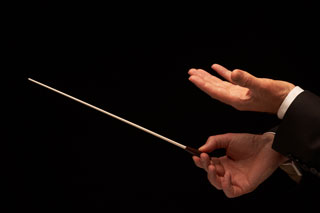 A close-up of a conductor's hands and baton