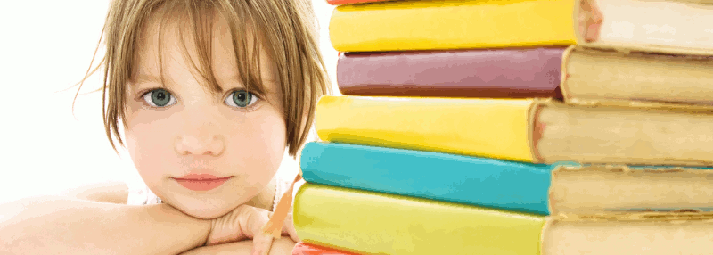 A young girl rests her chin on crossed arms beside a stack of text books